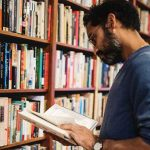 man glancing through a book he pulled off the library shelf in front of him