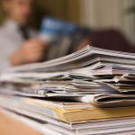 stack of magazines and newspapers with man reading article in background