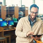 Man reading on tablet leaning on reference desk in library